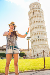 Funny young woman supporting leaning tower of pisa