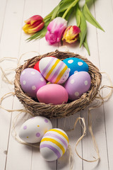 Fresh tulips and colorful easter eggs in a nest on a wooden tabl