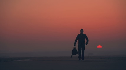 A man leaves the sunrise with a bag