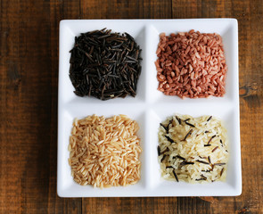 Different types of rice on plate on wooden background