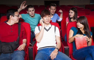Young men talking on the phone while watching movie at the cinem