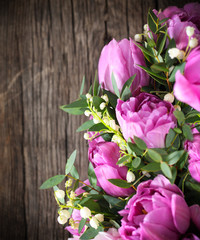 Bouquet of fresh pink tulips and lily of the valley on aged wood