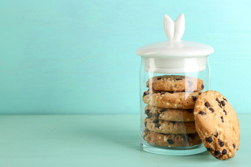 Tasty cookies in glass jar on color wooden background