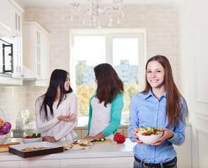 Cheerful teen girls preparing salad together
