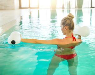 Blond young woman doing aqua aerobics