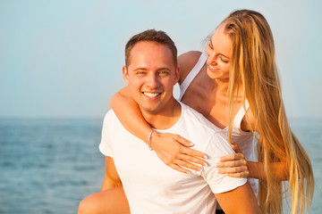 Laughing couple enjoying nature over sea background. Attractive