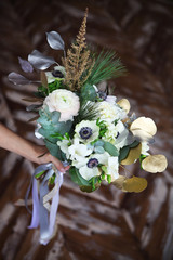 Wedding bouquet with ranunculus, freesia, roses and white anemon