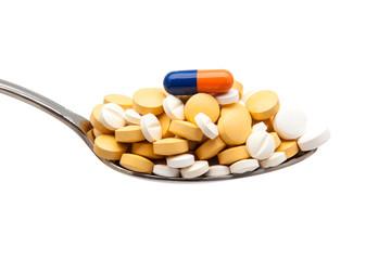 cuchara con píldoras y capsulas