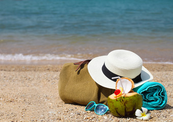 Straw hat, sunglasses, beach towel with beach bag and coconut co