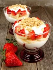 Strawberry and banana yogurt parfaits with granola on wood