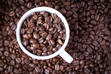 Coffee beans in coffee cup. Macro close up.