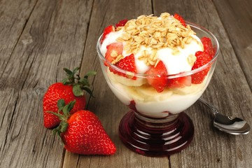 Strawberry and banana yogurt parfait with granola on rustic wood