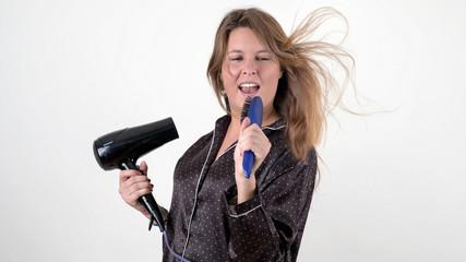Junge Frau singt in ihre Bürste beim Föhnen