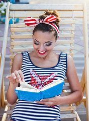 Beautiful pin up girl reading the book near the swimming pool