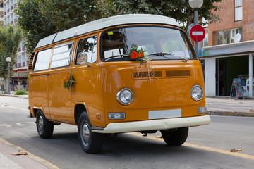 Orange minibus (minivan)  with white roof on the street.