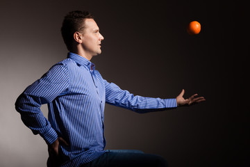 Diet and healthy nutrition. Man throwing orange
