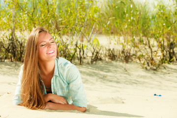 Young woman lying on grassy dune