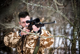 Hunting, army, military - sniper holding rifle and aiming