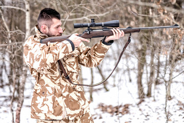 Hunter with sniper aiming and shooting in winter hunting season