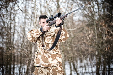 Sniper with weapon ready for combat or hunting in the forest