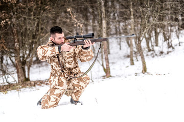 Professional hunter with sniper rifle aiming and shooting