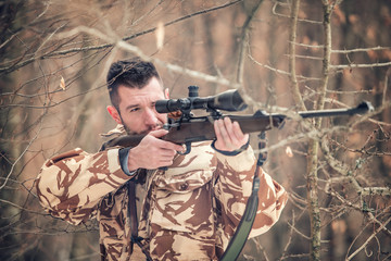 Man holding a sniper and shooting on an open season