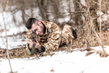 military man in combat holding a gun and shooting outdoors