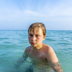 angry young boy in the beautiful ocean with sunburn