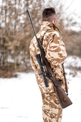 Portrait of military army man carrying a sniper rifle