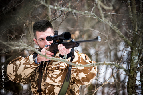 Hunting, army, military - sniper holding rifle and aiming - 78729816