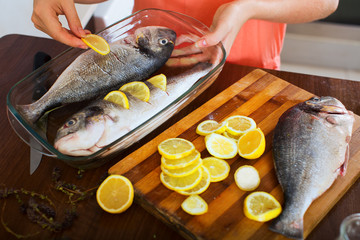 Close-up of woman putting pieces of lemon in fish