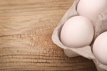 White eggs in the box on wooden background