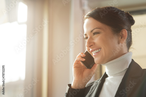 Attractive woman on the phone next to a window - 78732295