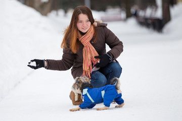 dog in blue overalls jumps for snow in  hands of girl in park