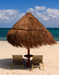 Umbrella and two chairs on sand beach