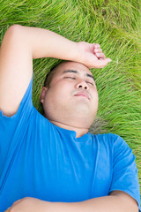 Stressful fat man is lying on the green grass with arm on his he