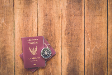 Thailand passport and compass on wood