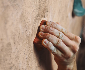 Man climbing up on wall in gym, close-up of hand