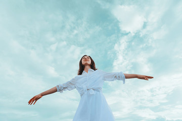 Young woman with raised arms enjoying a nice day