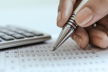 Woman auditing data printout with calculator