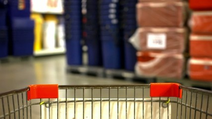 Customer shopping at supermarket with trolley and blurred