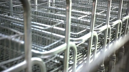 Rows of shopping carts on car park near entrance Of supermarket