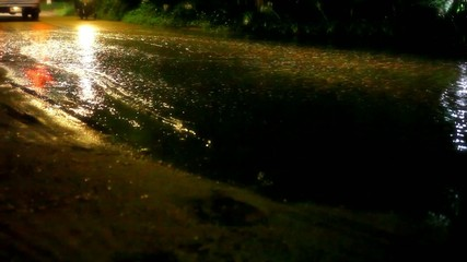 Car and motorbike drives through a puddle on the road at night