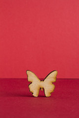 Wooden icon of butterfly on red background