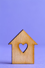 Wooden house with hole in the form of heart on purple background