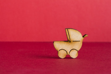 Wooden icon of baby carriage on red background
