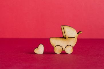 Wooden icon of baby carriage and little heart on red background
