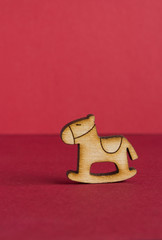 Wooden icon of children's rocking horse on red background
