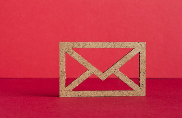 Wooden envelope icon on red background