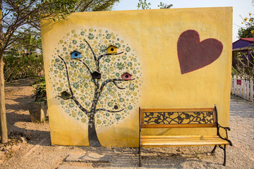 art tree painting on cement wall and yellow park bench.